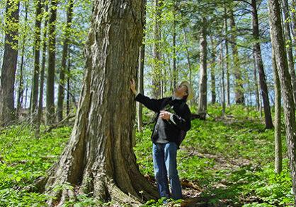 Man standing next to large tree